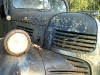 Sunlight Catches Head Lamp on old Rusty Truck